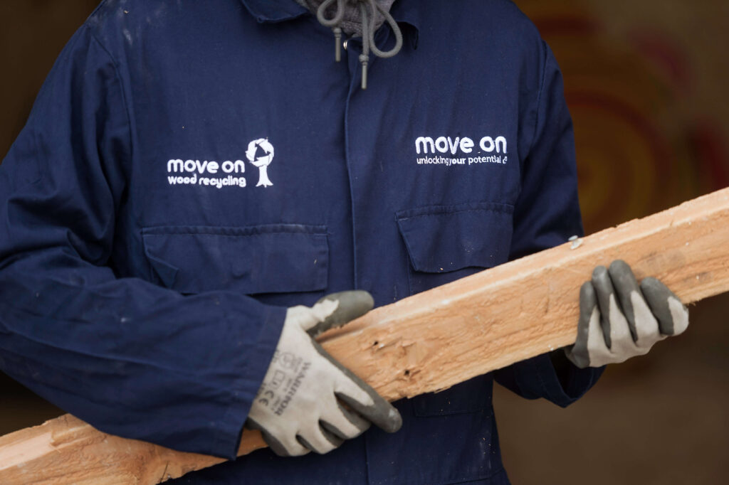 Move On Wood Recycling volunteer holding plank of wood